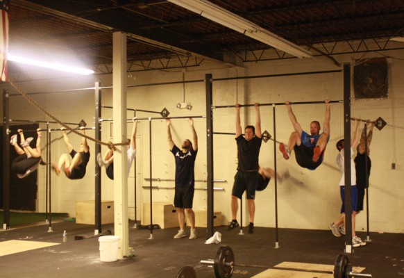 Group doing knees-to-elbows in CrossFit class