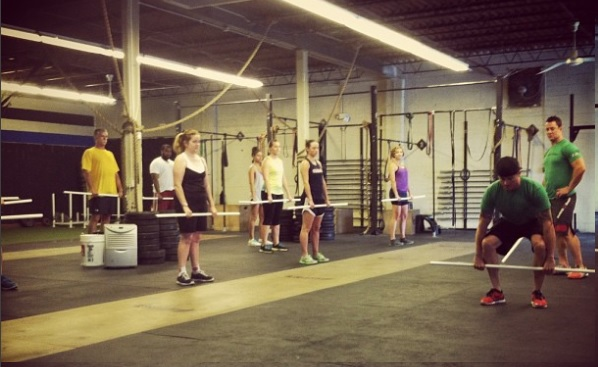 Coach Ronnie teaching the dead lift with PVC pipes to new members in the On Ramp class.